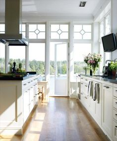 Kitchen with a view: White cabinets, black counters, floor to ceiling windows/doors.