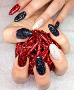 Pointed (stiletto) gel nails with red, white and black glitter with red tinsel.