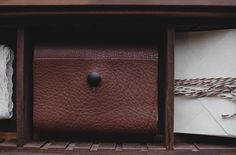Handmade leather satchels hold a variety of photographs. Add a vintage feel to your home by keeping it displayed on your coffee table or safely tucked away in one of our wooden heirloom boxes. #photostorage #photos #leather #handmade #satchel #folio  #blossombluephotography #BBPproducts