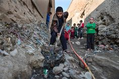 A boy shovels away raw sewage to clear a small polluted stream, Afghanistan, 2015, photograph by Paula Bronstein.