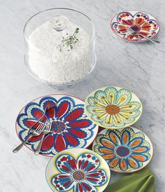 An exuberant flower in vivid, summery hues takes center stage on stoneware plates. Each plate is a combination of hand stamping and painting making each plate unique. A coordinating suite of four floral plates is sold separately.