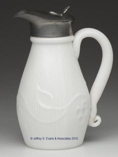 """BLOWN-MOLDED BELLFLOWER - SV MOLASSES JUG, opaque white, small-size ovoid body with an applied solid handle displaying a lower curl, plain base. Period hinged Britannia top without markings. Boston & Sandwich Glass Co. and possibly others. 1855-1875. 5 3/4"""" HOA, 4 5/8"""" H neck, 2 3/8"""" D base. <BR><I>Light crack to the lower handle terminal, otherwise undamaged.</I><BR>Literature: B & K I, fig. 1214. Belknap - Milk Glass, p. 87, pl. 77. Parallels the McKearins - American Glass, pl. 210, fig…"""