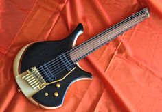 Mike Sankey – Black Swan «  Not only is it a headless ergonomic design, it also utilizes a multiscale fretboard for the seven strings; it is one of the only guitars in the world to combine this with a tremolo system. The unique headpieces, tuners, and bridge are made in Italy by T4M, and luxuriantly gold-plated to stand out from the crowd... – 1 of 3