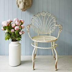 A beautifully weathered iron chair with a floral inspired back, it's just perfect for those sunny days.