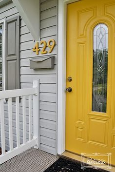 This makes me want to re-paint all of our doors! The yellow/gold looks gorgeous with the gray siding!! #exteriorpaintcolours #shadesofyellowpaintcolours
