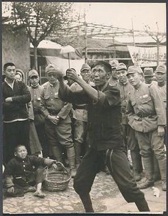 Japanese soldiers watch street performer in China.