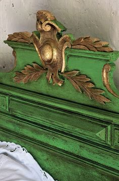 Headboard in green with gold carved detail. You can find similar shields to add to a headboard at www.buycarvings.com. Wild Goose Carvings' shield is hand carved in pine wood.