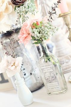 antique bottles and milk glass together create the perfect vintage wedding decorations. Just to few flowers, touch of silver and lace and ready to go. Southernvintagegeorgia rents all these elements to create this centerpiece.