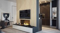 The living room features a slick, modern fireplace that uses natural wood paneling and brings some warmth to the otherwise angular design.