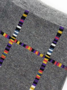 multicolour striped strips. Sadly, it's from a japanese site that is now throwing a 404. I'm guessing the vertical stripes are intarsia done with a very fast-changing sock yarn. I wonder if the horizontal stripes might be duplicate stitch or other embroidery.