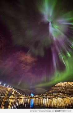 Northern lights over Tromsø, Norway - Amazing scenery with Aurora borealis (northern lights) in the night sky over the city of Tromsø in Norway with Ice Sea cathedral shining blue.