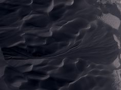 """A piece of Mars: An elegantly swirling gully has carved itself into the side of a dune field. These """"dune gullies"""" are unique to the southern midlatitudes, and their formation is not well understood. Regardless of how they form, they do change in successive images, indicating that they are active today. They provide yet more evidence of active geological processes on Mars. (HiRISE PSP_006648_1300)"""