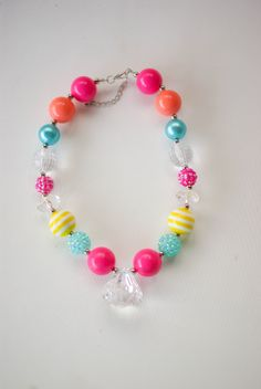 A bright colored bubble gum necklace Has large chunky beads and a large clear 'diamond'. Sized for a Toddler/Child Perfect for dress up or photoshoots.  Looking for a matching Headband or