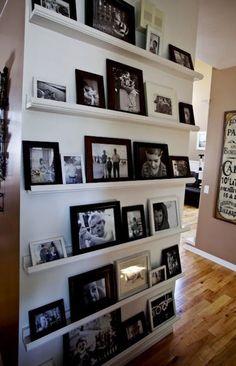 #Fotomuur in de #hal met verschillende #lijsten in #zwart en #wit op #planken aan de muur. #pictures #wall #hallway #black #white