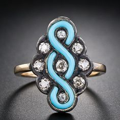 The turquoise color portion which comprises the center of this exotic and unusual antique ring is probably some type of glass or enamel, not the stone. In any case, the entrancing 'infinity' motif is embellished inside and around with sparkling old mine-cut diamonds with a brownish tinge and set in darkly oxidized silver over gold. Something different and dramatic in an antique ring. Victorian