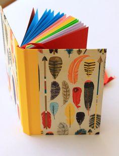 Plumas! - Cuaderno MOW, 100 hojas papel bond de variados colores, tapa forrada en papel, lomo vinilo amarillo, Cinta separadora y hojas de guarda color rojo.