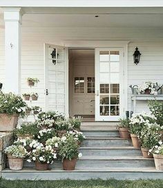 In this photo: White flowers—including salvia, violas, petunias, begonias, and lantana—adorn the side porch. like the terra cotta pots on gray porch Modern Farmhouse, Farmhouse Style, Vintage Farmhouse, White Farmhouse, American Farmhouse, Farmhouse Garden, Outdoor Spaces, Outdoor Living, Farmhouse Front Porches