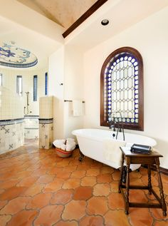 floor tile, clawfoot tub, stained glass, tiled cove ceiling, tiled chair rail.