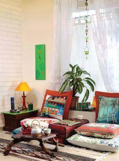 salon marocain moderne, vieille valise comme table, petite table en bois et plusieurs coussins