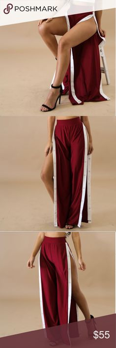 Burgundy Red Open Side Snap Trackpants Burgundy red, white side stripe Stretch Fabric Double Side Snap button up closure Thick elastic waistband Wide leg 85% Nylon 15% Spandex All pictures taken exclusively for Style Link Miami and are showing actual product. Style Link Miami Pants