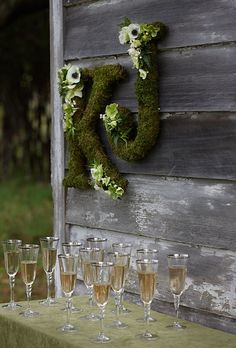Moss Monogram Designate the toasting area with a set of artful initials—or spell out a sentimental message of love. Clusters of anemones, helleboruses, and jasmine leaves add a sweet flourish. Moss-covered letters, $79 each, The Magnolia Company. Flutes and tablecloth, Classic Party Rentals.
