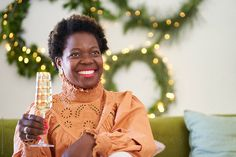 Portrait of a beautiful young african woman holding a champagne glass at home in her living room with Christmas decorations in the background. Stylist: Bielle Bellingham Photographer: Micky Wiswedal African Women, Champagne, Stylists, Christmas Decorations, Living Room, Woman, Portrait, Glass, Beautiful