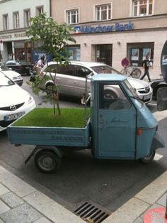 Vespacar advertising a Munich cafe with trees and grass
