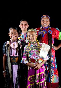 Pow wow friends Aarora Piper, Jaydean, Bailee and Shandiin Horton all dressed in dance regalia pose as a group against a black background