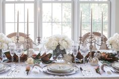 If you're looking for inspiration for your holiday table settings, consider a neutral table with white roses and magnolia leaves.
