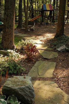 Flagstone path through woods w nice small shrubs and a bench or two.