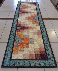 Create a bright mood on any table with this lovely quilted batik bargello table runner. Bright light blues, deep crimson, peach and creams make this bargello runner perfect for adding a splash of color to any room. • Measures: 16.5 x 52 • MULTIPLE PURCHASES: If you intend to