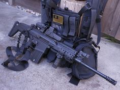 Mk 17 SCAR-H 7.62mm. One point sling attached. Two optical sights mounted? Vertical foregrip mounted. Flag of taiwan on web gear behind the rifle.