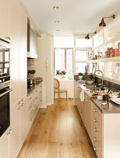 I love how they took a standard galley style kitchen and switch it up a bit. The usage of windows and a shelf on one wall is wonderful.