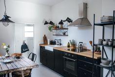 Czarne szafki i drewniany stół w aranżacji kuchni z jadalnią - Lovingit.pl