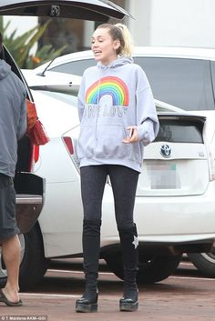 Peace, man: The pop star, 24, wore a gray hoodie with a rainbow and the words 'One Love' on the front and showed off her slim frame with a pair of black leggings and knee-high boots