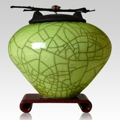 The Raku Lime Green Multi Family Cremation Urn is very durable and made by the way that raku has been made 100's of years ago. Tradition is a big part in the making of this urn and will create a peaceful tribute for your loved one. The lids are decorated with black bamboo and a Zuni inspired gem stone; the color is vibrant. The random raku crazing effects can be seen all through the stylish patterns.