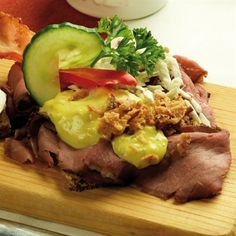 Smørrebrød - An open face sandwich with thinly sliced roast beef, remoulade and fried onions on top.