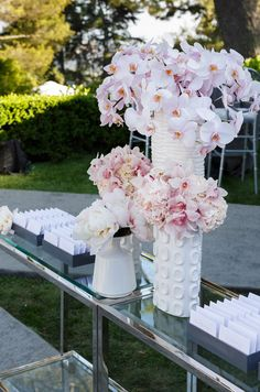 Romantic pink florals in architectural white containers separate two sets of elegant escort cards.