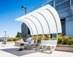 Sleek bus stop at Varian Medical Systems in Silicon Valley. This piece of urban furniture was crafted by Bike Arc, which also has a similar design that combines these covered benches with bicycle racks in one structure.