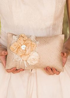 """This Burlap Chic Ring Pillow is the perfect combination of rustic and vintage. The burlap gives it a shabby chic look and the delicate floral details and lace trim make it a perfectly sweet and sophisticated accessory for a vintage inspired wedding. Use it after your wedding as a decorative pillow in your home. Features and Facts:  Measurements: 23"""" W x 5.98"""" H.  Material: Burlap Polyester  Tie wedding rings to pillow using the ribbon."""