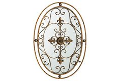 A rusted metal fleur-de-lis motif rests above mirrored glass, creating an appealing sense of depth and history.