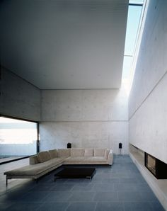 Living Space. Room. Spacious. Skylight. Design. Fireplace. Minimalist. Modern. Slate Floors. Concrete. White. Light. Decor. Interior. Home.
