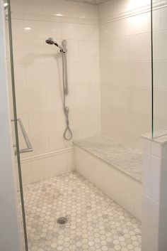 source: Lamantia website Stunning walk-in shower with oversize white ceramic tile laid in a staggered brick pattern. Bench over stairs - How Do It Info