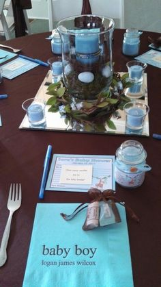 Table centerpiece made with candle in bird's nest surrounded by light blue robin's eggs resting on green moss.
