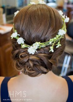 Spring wedding hairstyle ideas: Embrace your inner flower child with a low chignon and pretty floral crown. Hair & Makeup by Steph