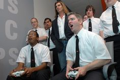 Geek Squad founder Robert Stephens plays Call of Duty 3 on the XBox 360 in the employee lounge as Fabio looks on to celebrate the opening of Geek Squad City.
