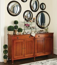 Convex mirrors in varying sizes turn a bit of wall over a buffet into a mirrored gallery wall.