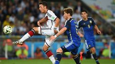 Mesut Oezil of Germany (8) controls the ball against Lucas Biglia of Argentina (6).