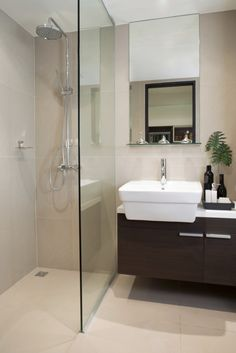A modern bathroom with a single pane of glass separating the vanity from the tile shower. The vessel sink dominates the slim dark wood vanity, topped by a mirror with a built-in plexiglass shelf.