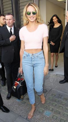 Candice Swanepoel combines a pink fuzzy cropped sweater with mom jeans.